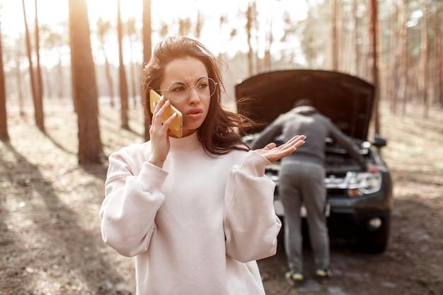 De auto begaf het. de man probeert de auto te repareren. een jonge vrouw belt en vraagt om hulp bij de dienstverlening