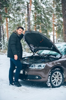 De auto begaf het. mooie jonge bestuurder probeert de auto in het bos in de winter te repareren.
