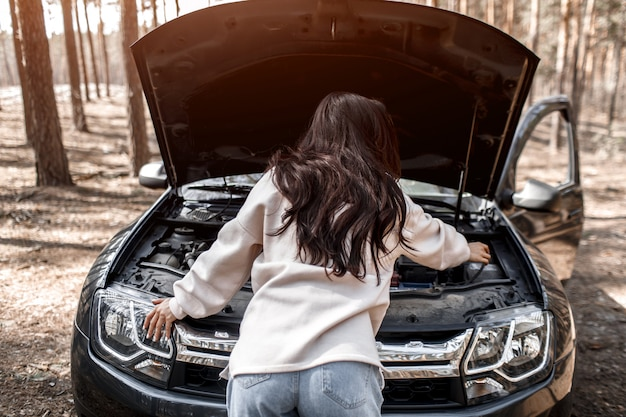 De auto begaf het. ongeval onderweg. een vrouw deed de motorkap open en controleert de motor en andere details van de auto