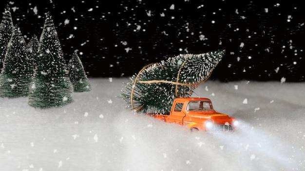 De auto draagt de boom 's nachts uit het bos. auto in de sneeuw. kerst achtergrond. banier