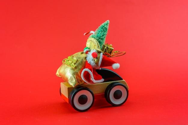 De auto draagt de kerstman met geschenken op een rode kerstachtergrond.