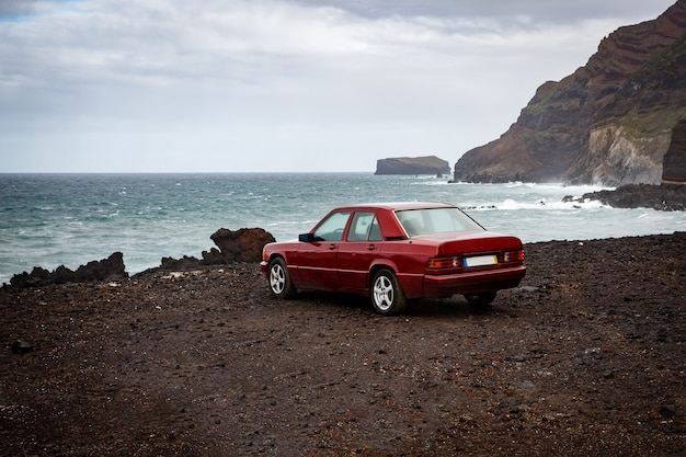 De auto in de buurt van de oceaan, rotsachtige kust.