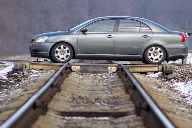 De auto is in beweging. de auto steekt de spoorlijn over.
