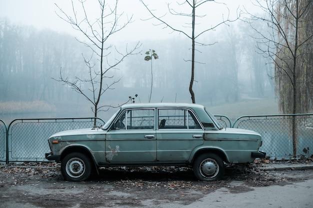 De auto is 's ochtends bij het meer in het mistige donkere park verloren