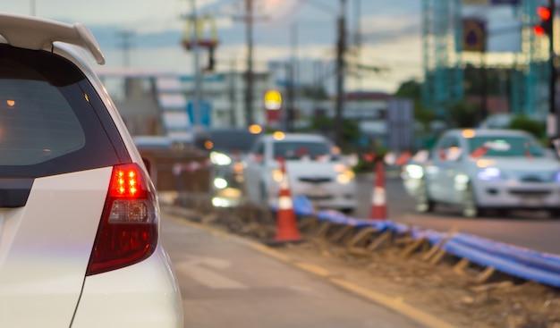 De auto laat zien dat het remlicht geparkeerd is op het kruispunt van verkeerslichten.