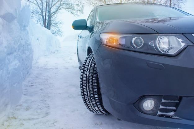 De auto op een achtergrond van een grote laag sneeuw