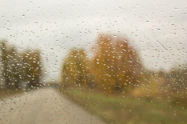 De auto rijdt langs de herfstweg met regendruppels op het autoraam van de voorruit