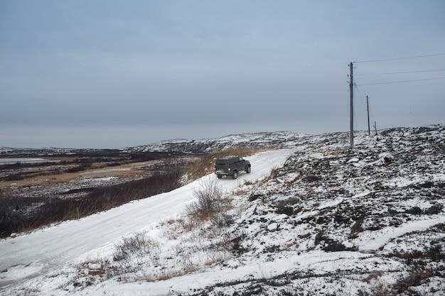 De auto rijdt op een moeilijke, ijzige weg. gladde arctische weg door de heuvels. winter teriberka.