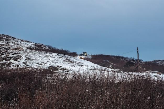 De auto rijdt op een moeilijke, ijzige weg