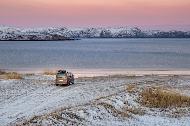 De auto staat geparkeerd aan de oever van de noordelijke ijszee. reisconcept van reizen met de auto. prachtig uitzicht op de noordelijke baai in het dorp teriberka.