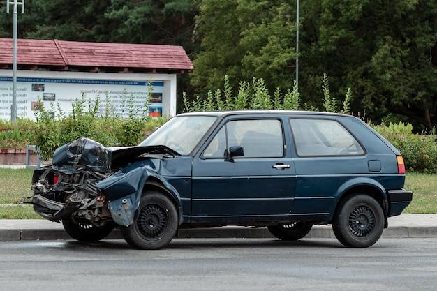 De auto staat geparkeerd na het ongeval, de motorkap is kapot, de gevolgen van onoplettendheid op de wegen.