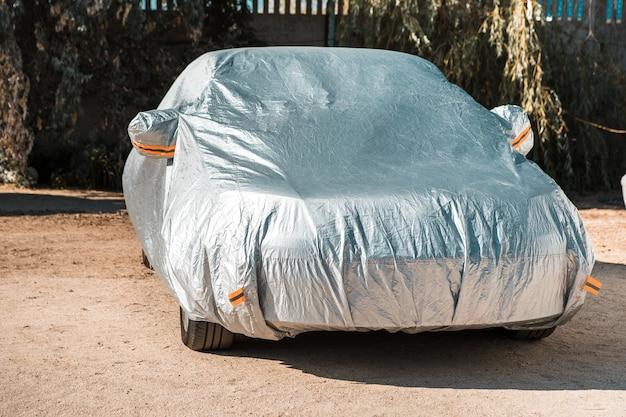 De auto staat op de parkeerplaats met autodekking tegen de zon. bescherming tegen het verwarmen van de auto.