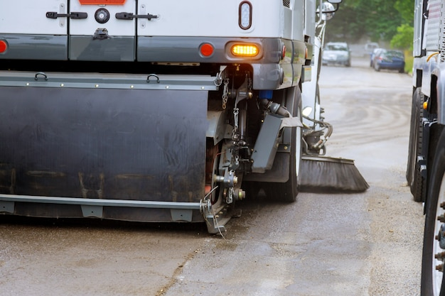 De auto van de straatveger maakt de machine in de gemeentelijke auto schoon voor het buitenshuis schoonmaken van de trottoirs van borstelwegen.