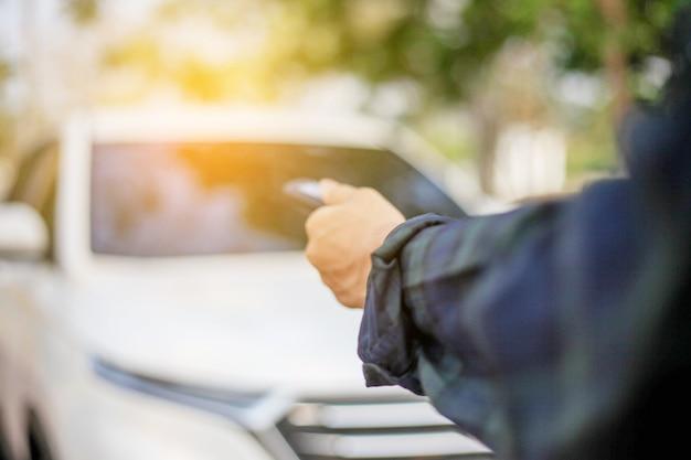 De auto verre sleutel van de mensenholding op witte auto