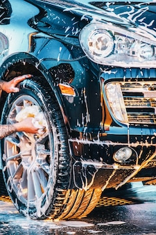 De auto wassen. een zwarte auto wassen bij een wasstraat. schone auto