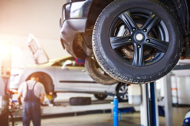 De auto wordt voor reparatie opgetild in een autoservicestation