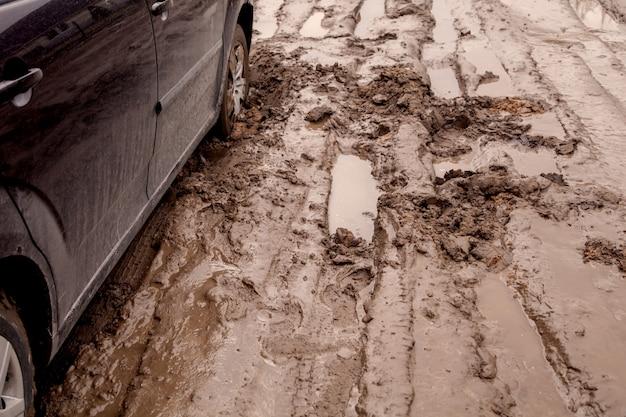 De auto zit vast op een slechte weg in de modder