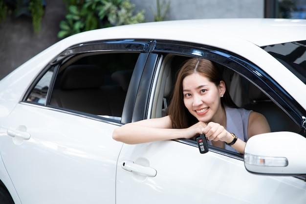 De autobestuurder die van de vrouw en nieuwe autosleutels glimlacht toont.