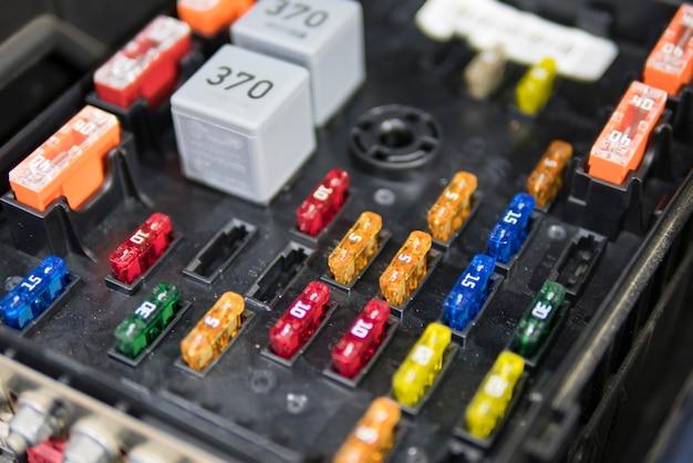 De autoelektricien herstelt auto, gekleurde zekeringen