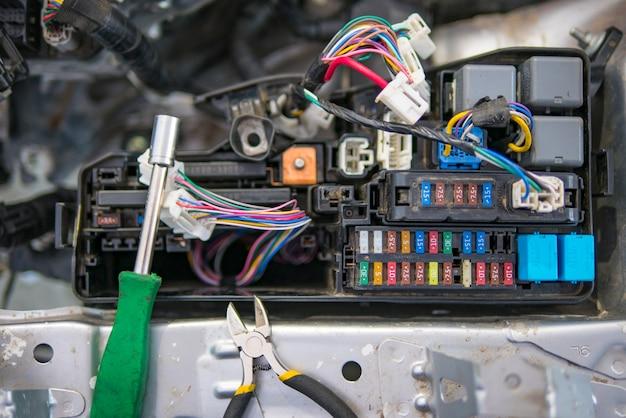 De autoelektricien herstelt auto, meetapparaat en fuses en tangen