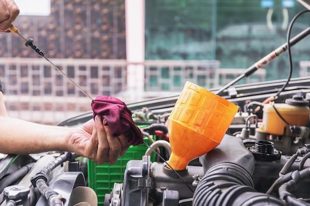 De automonteur controleert het motoroliepeil op de motoroliepeilmeter van de auto-, auto-industrie en garageconcepten.