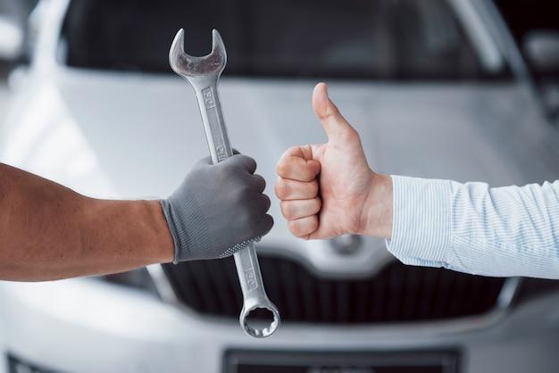 De automonteur houdt de sleutel in de hand van de cliënt en tilt zijn duim op. goed werk