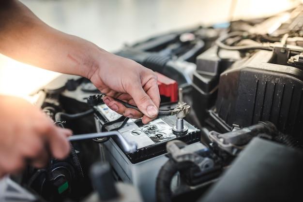 De automonteur staat op het punt om de batterij te verwijderen om de nieuwe batterij van de auto in de autoreparatiewerkplaats te vervangen.