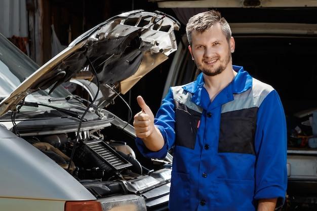 De automonteur werkt in de garage.