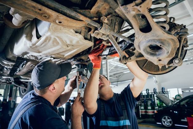 De automonteurs herstellen autoschorsing van opgeheven auto bij reparatiebenzinestation