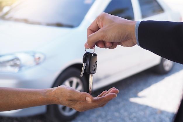 De autoverkoper en de sleutel tot de nieuwe eigenaar.