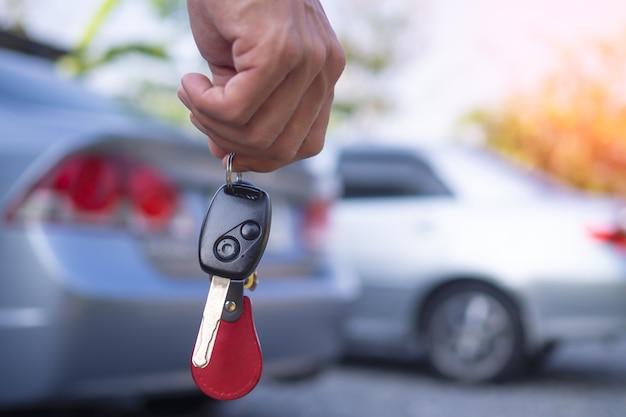 De autoverkoper en de sleutel van de nieuwe eigenaar.