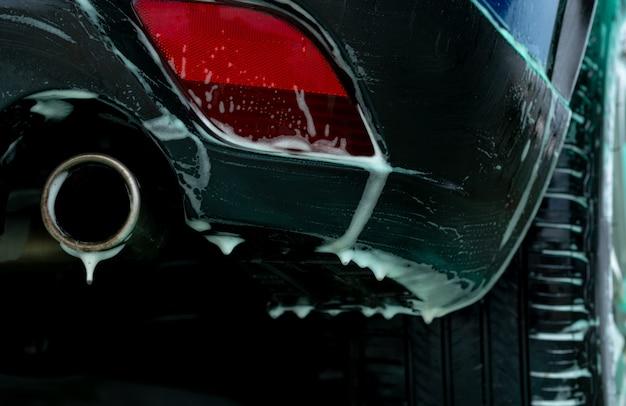 De autowasserette van close-up blauwe suv met wit zeepschuim. autoverzorgingsbedrijf.