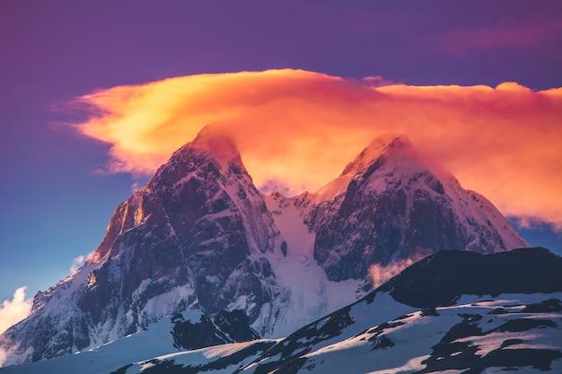 De avondmening van de zonsondergang over de sneeuwbergketen