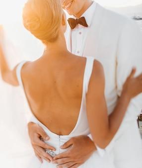 De avondzon glanst over mooi huwelijkspaar die vóór het overzees koesteren