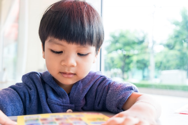 De aziatische 3 éénjarigenjongen leest prentenboek met exemplaarruimte.