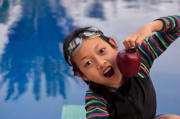 De aziatische appel van de meisjeholding bij het zwembad met slijtage zwembril