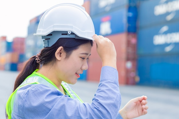 De aziatische arbeider van de meisjestiener in het verschepen van vrachthavenwerk en beheert de veiligheid van de containers van de invoeruitvoer van goederen met witte helm.