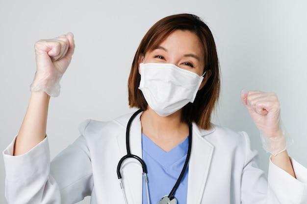De aziatische arts draagt het medische masker om infectie tegen kiem, bacteriën, covid19, corona, sars, griepvirus op witte achtergrond te beschermen en te bestrijden.