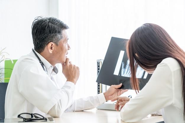 De aziatische arts en de patiënt bespreken