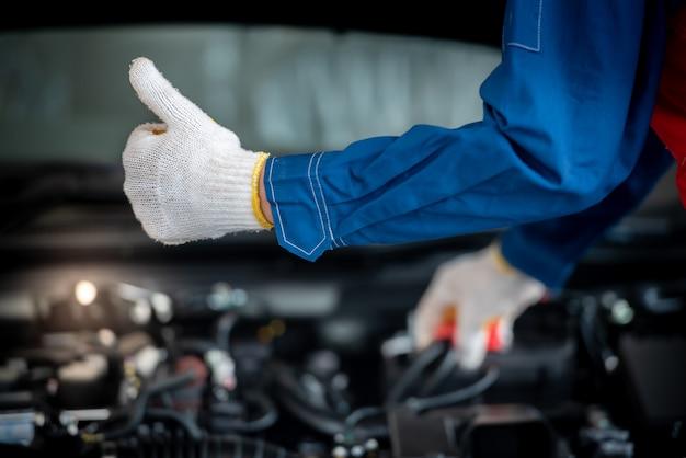 De aziatische automonteur in een autoreparatiewerkplaats controleert de motor. voor klanten die auto's gebruiken voor reparatiediensten, zal de monteur in de garage werken.