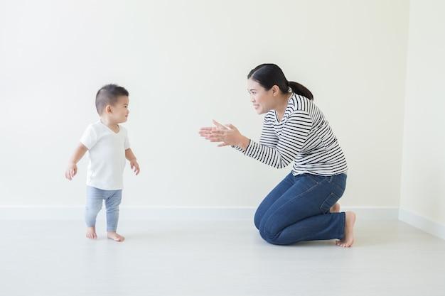 De aziatische babyjongen die met het letten leren te lopen en door mamma te nemen, zoon neemt thuis de eerste stappen