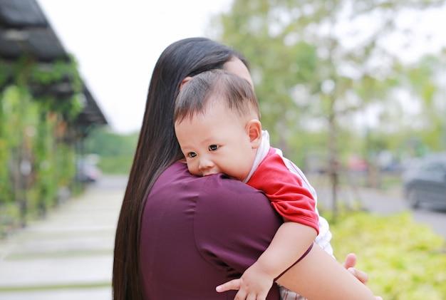 De aziatische babyjongen die van de close-up in omhelzing van moeder ligt