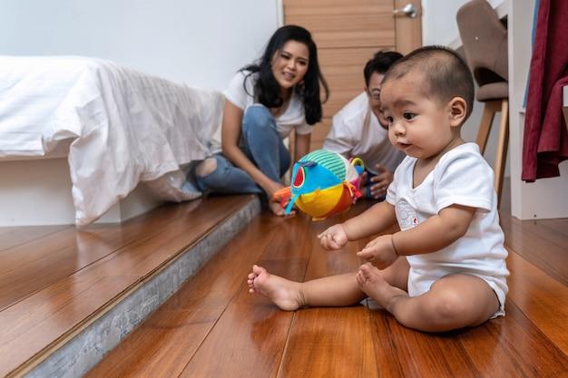 De aziatische babyjongen kruipt en speelt de bal op de houten vloer over de vage foto