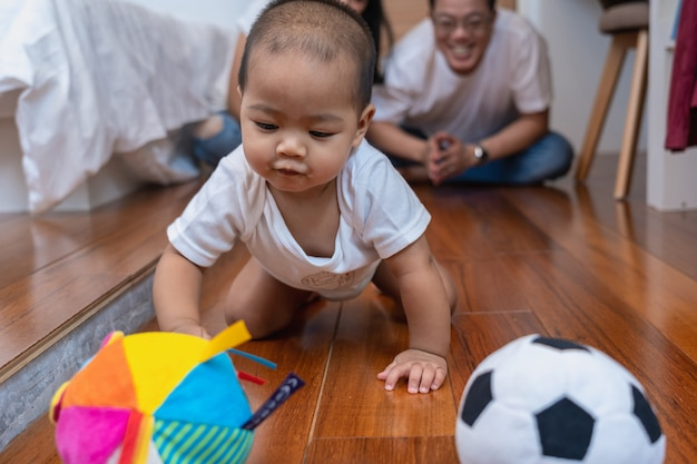 De aziatische babyjongen kruipt en speelt de bal op de houten vloer