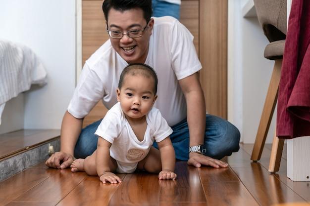 De aziatische babyjongen kruipt op de houten vloer over de vader en de moeder in de slaapkamer