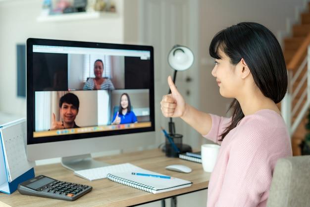 De aziatische bedrijfsvrouw beduimelt omhoog aan haar collega's over plan in videoconferentie