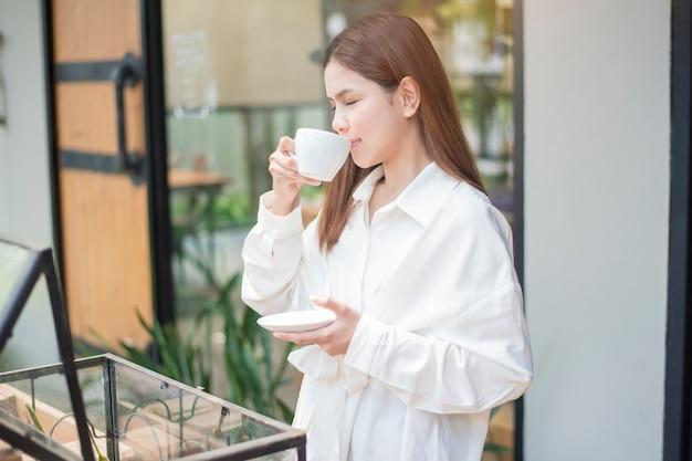 De aziatische bedrijfsvrouw drinkt koffie in de ochtend bij koffiewinkel