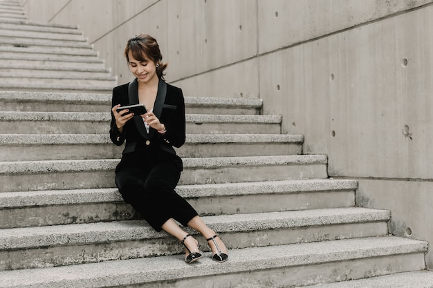 De aziatische bedrijfsvrouw glimlacht en zit op trede. ze is aan het chatten met haar baas