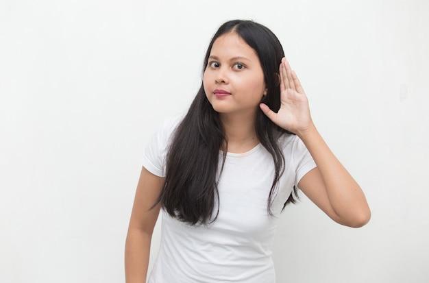 De aziatische bedrijfsvrouw houdt haar hand dichtbij haar oor en luistert