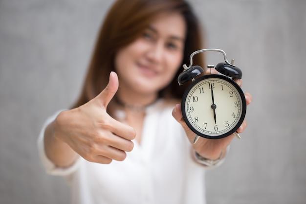 De aziatische bedrijfsvrouw toont duimen met een klok voor goede tijd of goed beëindigt baan op tijd concept